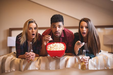 Friends look shocked watching TV. photo by Shutterstock