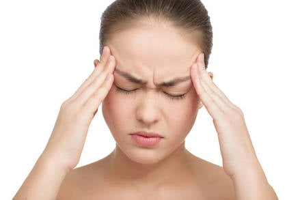 woman winces in pain rubs temples - headache