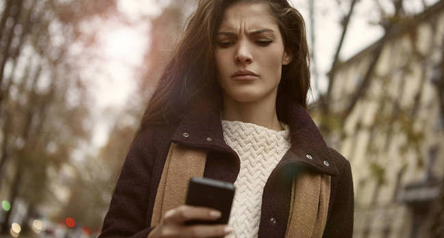 An angry woman looking at her phone