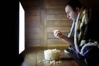 A man watching a screen and eating popcorn