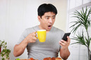 Surpised man mobile phone photo by Shutterstock