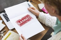 person opens letter reading 'banned'
