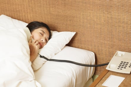 woman answers phone in the middle of the night. photo by SHutterstock