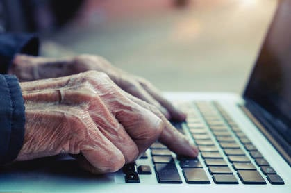 Old man's hands typing on laptop