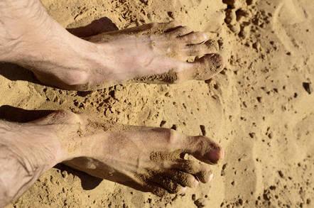 Feet on hot beach sand