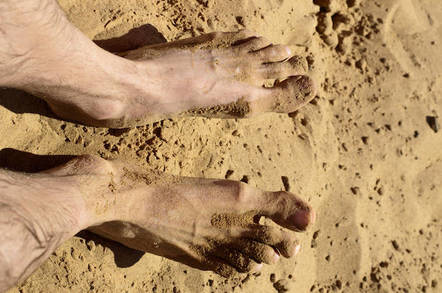 Feet on hot beach sand