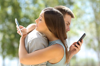 Couple on phones photo via Shutterstock
