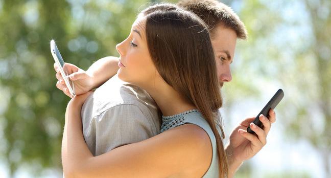 Couple on phones photo via Shutterstock