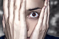 Person hides face in shocked anticipation of something horrible. Photo via shutterstock