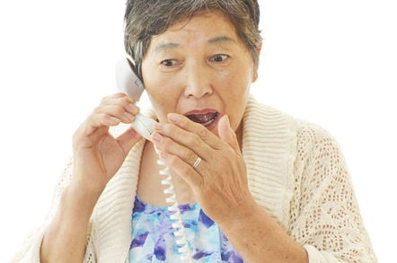 Older woman with shocked expression speaks on fixed line phone... photo by Shutterstock