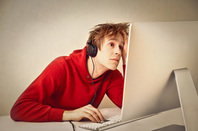 Kid on computer, photo via Shutterstock