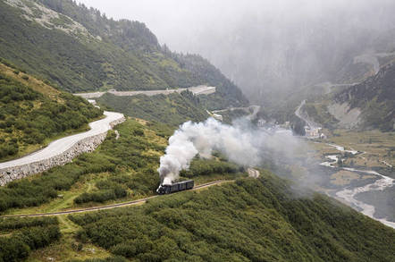 Train in the Alps emerges from clouds. Photo by Shutterstock