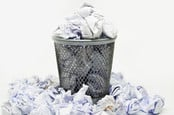 Wire wastepaper bin filled with scrunched up paper. Photo by Shutterstock