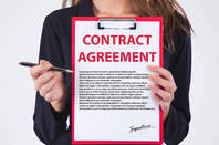 woman holds contract agreement to sign