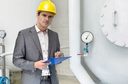 Man with clipboard, hardhat and concerned expression next to a pressure gauge in an industrial setting. Pic by Shutterstock