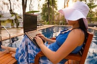 Woman works from laptop by the pool. photo by sHutterstock