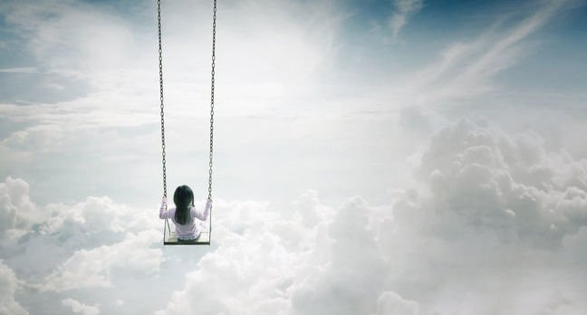 Girl on a swing above the clouds. Photo by shutterstock