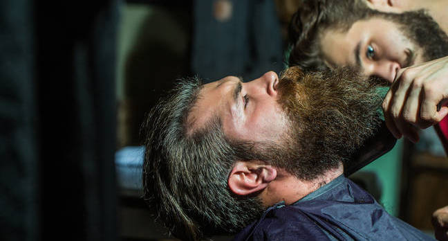 Beardy hipster trims beard of second beardy hipster. photo by Shutterstock