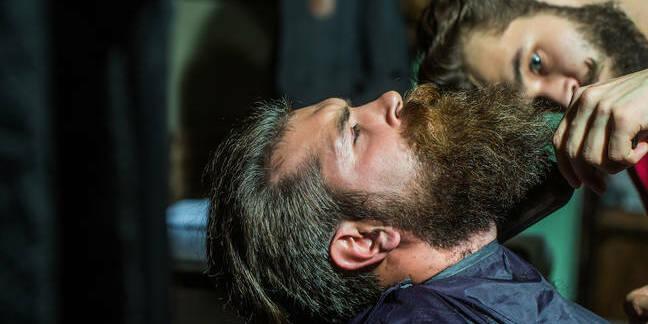 Beardy hipster trims beard of second beardy hipster. photo by Shutterstock