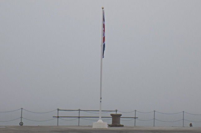 A Union Flag stands limp in fog at HM Naval Base Portsmouth