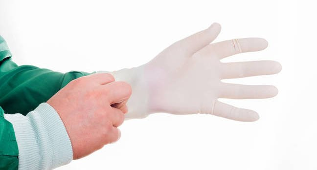 Hand pulls on a latex rubber glove (disposable). Photo by shutterstock