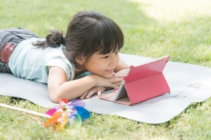 child browsing on tablet outdoors. pHOTO BY SHUTTERSTOCK