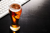 Desk beer - pint at a keyboard. Photo by shutterstock