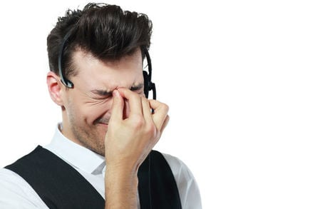 Call centre worker looks frustrated and unhappy. Photo by Shutterstock