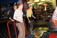3 young people playing Playstation's Dance Dance Revolution (DDR)