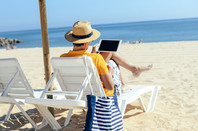 Man browses his tablet and ignores the beach. Photo by shutterstock