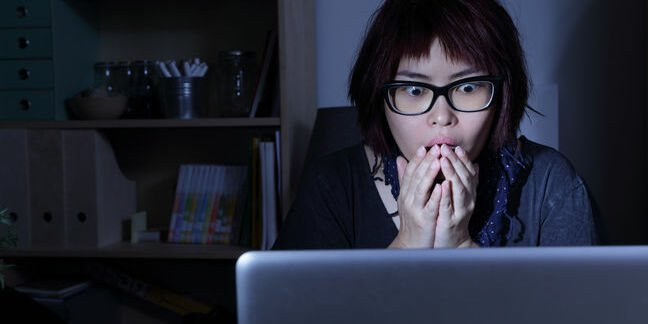 Woman stares at laptop screen, shocked. Pic by shutterstock