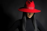 Woman in ret hat photo via Shutterstock