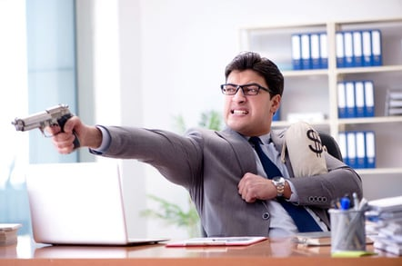 Businessman with money bag and gun photo via Shutterstock