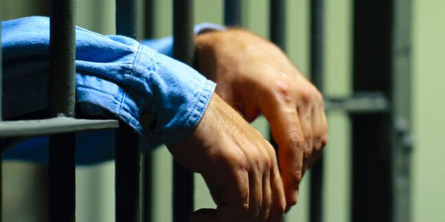 hands through the jail bars. Photo by shutterstock