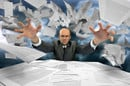 Man vs paperwork. Paper-pusher loses control. Photo by Shutterstock
