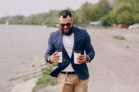 Man carries two cups of coffee walking on a beach