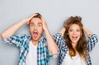 Shocked couple scream and clutch their hair