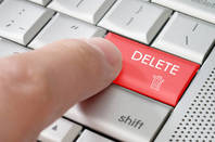A finger pressing a delete key