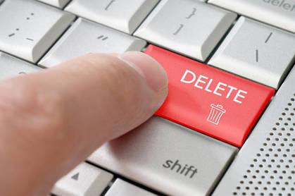 A finger pressing a delete key