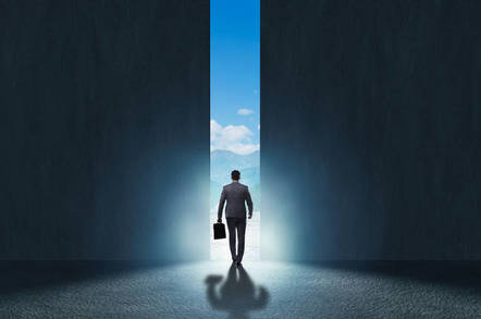 Business suit wearing man walks out of closing door in darkened room into the bright sunlight and blue sky