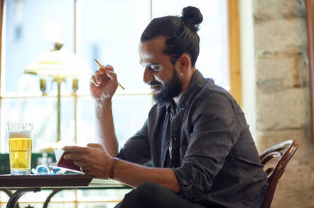 Man with bun sucks on vape. Photo by shutterstock