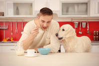 Man and dog eat dog food. pic by shutterstock