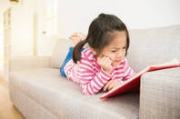 Little girl concentrates hard on a book she's reading