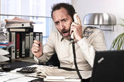 Upset man at desk shouts into phone. Pic: Shutterstock