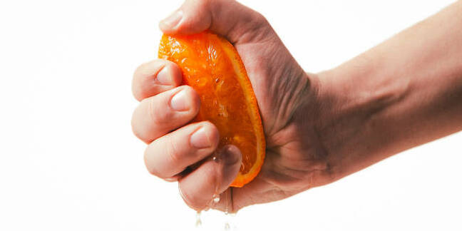 A hand squeezing juice from an orange