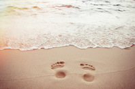 Footprints sand photo via Shutterstock