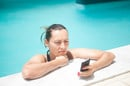 Annoyed-looking woman squints at mobile phone screen while in swimming pool.
