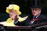 prince phil and queen elizabeth wave from carriage.