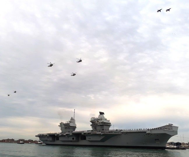 Royal Navy aircraft fly over HMS Queen Elizabeth as she enters Portsmouth Harbour. Pic: Gareth Corfield