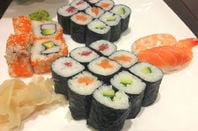 Sushi platter containing uramaki, hosomaki, nigiri and California roll with picked ginger and wasabi